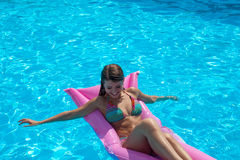 Girl on inflatable mattress in pool. Girl in colorful bikini on inflatable mattress in pool Royalty Free Stock Photos