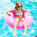 Girl on inflatable ring in swimming pool Stock Photos