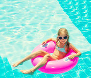 Girl on inflatable ring in swimming pool Stock Photo