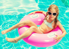 Girl on inflatable ring in swimming pool Stock Image