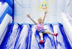 Girl with inflatable slides rolls Royalty Free Stock Photo