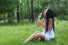 Girl inflates the bubbles Royalty Free Stock Photography