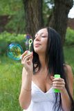 Girl inflates the bubbles Royalty Free Stock Photo