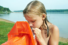 Girl inflates orange mattress on beach Stock Photography