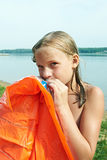 Girl inflates orange mattress on beach Royalty Free Stock Photo