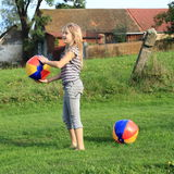 Girl with inflating balls Stock Image