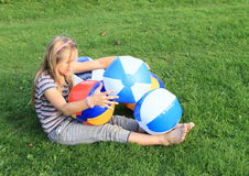 Girl with inflating balls. Little girl - smiling barefoot kid playing with planty of inflating balls Royalty Free Stock Image