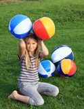 Girl with inflating balls Stock Photography