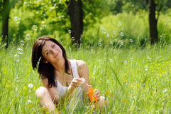 Girl inflating soap bubbles Stock Photos