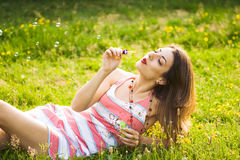 Girl inflating soap-bubbles Stock Images