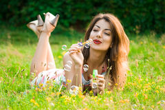 Girl inflating soap-bubbles Royalty Free Stock Images