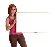 Girl with information board. Young red-haired woman showing an empty noticeboard isolated on white royalty free stock photo