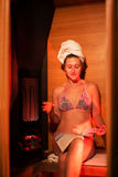 Girl in an infrared sauna is drinking tea and reading a magazine Stock Photos