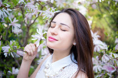 Girl inhales the aroma of blooming magnolias Royalty Free Stock Image