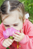 Girl inhales the scent of a peony flower Stock Photo