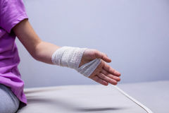 Girl with injured hand sitting on stretcher bed Stock Photography