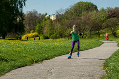 Girl on inline skates learns to ride Royalty Free Stock Image
