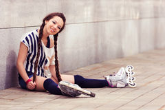 Girl on inline skates sitting and resting Royalty Free Stock Image