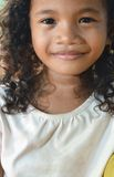Girl with innocent smile. A portrait of a innocent southeast asian girls with curly hair and a calm happy smile stock photo