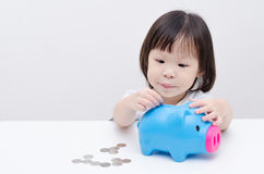 Girl insert coin into piggy bank Royalty Free Stock Images