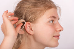 Girl insertin hearing aid into ear Stock Images