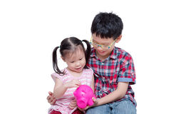 Girl inserting coin into piggybank with her brother Royalty Free Stock Photo