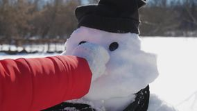 Girl inserts a nose on the snowman. The child plays with a snowman. Winter happy time, kid on snow. stock video