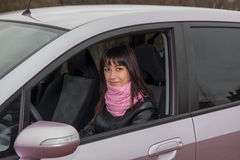 Girl inside pink car. Girl with pink scarf inside pink car Royalty Free Stock Photo