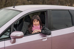 Girl inside pink car. Girl with pink scarf inside pink car Stock Image