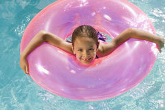 Girl Inside Pink Float Tube In Pool Royalty Free Stock Image