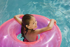 Girl Inside Pink Float Tube In Pool Stock Images