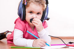 Girl inspired with music drawing. Little girl playing with headset and crayons on the floor Royalty Free Stock Photography