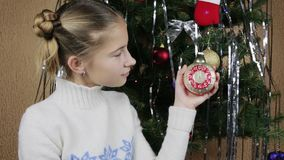 Girl with interest looking at vintage Christmas toy alarm clock. Imitates with his finger the ticking of the Christmas clock stock footage