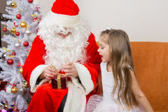 Girl with interest looks like Father Christmas helps to open her gift Stock Photography
