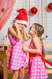 Girl with interest whispers something to another girl in a New Years cap. Two funny sisters four girls and six years of playing and having fun in the home New Stock Photography