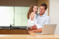 Girl is interested in her fathers laptop Stock Images