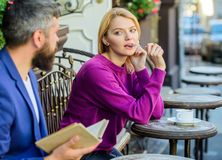 Girl interested what he reading. Guide to dating. Meeting people with similar interests. Man and woman sit cafe terrace. Girl interested what he reading. Guide stock photography