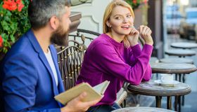 Girl interested what he reading. Meeting people with similar interests. Man and woman sit cafe terrace. Literature. Girl interested what he reading. Meeting stock photos