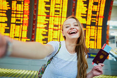 Girl in international airport, taking funny selfie with passport and boarding pass near flight information board Stock Images