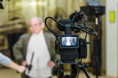 The girl interviews the man. Video shooting in the interior. LCD display on the camcorder stock photos