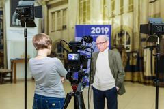 The girl interviews the man. Video shooting in the interior. LCD display on the camcorder royalty free stock images