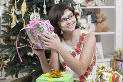 Girl is intrigued with Christmas gift Stock Photo