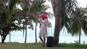 Girl with ipad and bagage. In the palm forest near sea stock footage
