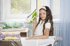Girl with iron. Cloth cleaning Royalty Free Stock Photography
