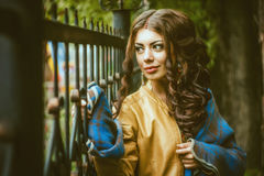 The girl at the iron fence. Beautiful girl standing at the iron fence and touches his hand Stock Photo
