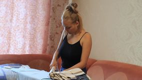 Girl ironed clothes with iron on ironing board.  stock footage