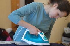 Girl irons clothes with iron Stock Image