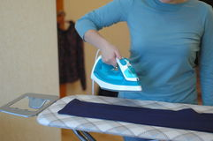Girl irons clothes with iron Royalty Free Stock Image