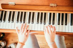 Free Girl Is Playing Piano At Home, High Angle View, Blurry Background Stock Photography - 142085422