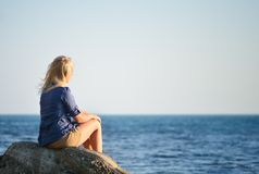 Girl Is Sitting On A Rock And Looking At The Sea Stock Photo